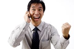 Business Celebration. A young asian businessman celebrates his success on the phone Stock Images
