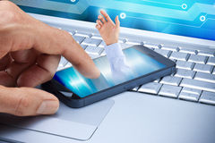 Business Cell Phone Contact Computer. A cell phone on a laptop computer keyboard with a hand coming out of the screen to make contact Stock Photo