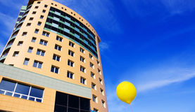 Business center Against the blue sky  on a background of a yello. Business center on a background of a yellow air balloon, a symbol of successful business Royalty Free Stock Image