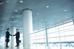 Business center. One of floors of modern business center with two partners handshaking Royalty Free Stock Photo