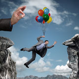 Business challenge. Businessman holding on to balloons above a cliff trying to escape hand bursting his balloon and bridge the gap concept for business adversity Stock Image
