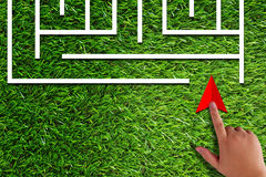 Business Challenge Concept. Business challenge, finding solution, resolve problem concept, hand holding red arrow and maze on green grass background Stock Images