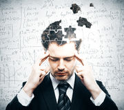 Business challenge concept. Portrait of pensive young businessman with puzzle piece head on grey background. Business challenge concept Stock Images