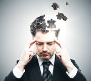 Business challenge concept. Portrait of pensive young businessman with puzzle piece head on grey background. Business challenge concept Royalty Free Stock Images