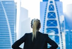 Business challenge. Confident businesswoman overlooking the city center high-rises royalty free stock photography