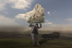 Business Challenge. Business man outdoor, struggling to hold a big rock above him. Concept for challenge, stress, problems Royalty Free Stock Photo