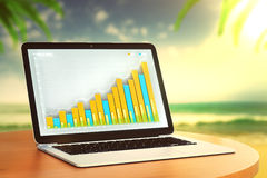 Business chart on laptop desktop on round wooden table Stock Photo