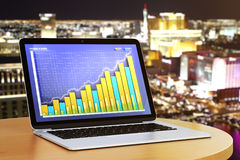 Business chart on laptop desktop on round wooden table at night Royalty Free Stock Image
