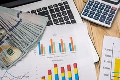Business chart, laptop, pen, dollar and calculator. Office workplace - business chart, laptop, pen, dollar and calculator Royalty Free Stock Photo
