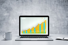 Business chart on laptop screen with coffee cup and diary at con Royalty Free Stock Photos