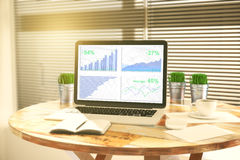 Business chart on laptop screen with diary, buckets of grass and Royalty Free Stock Image