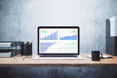 Business chart on laptop screen with other accessories on wooden. Table, close up Stock Photography