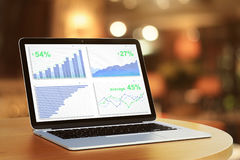 Business chart on laptop screen on round wooden table Royalty Free Stock Photography