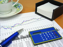 Business chart and office objects 2. Business charts, calculator, blue pen, notes holder and coffee cup Stock Images