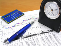Business chart and office objects. Business charts, calculator, blue pen and desk clock Stock Photos