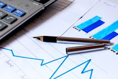 Business chart showing financial growth. Pen placed over financial statistics and charts Royalty Free Stock Photo