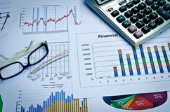 Business charts and graphs with eye glass and calculator Royalty Free Stock Image