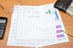 Business charts with money, calculator, glasses and pen Stock Photos