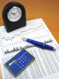 Business charts and office objects 3. Business charts, calculator, blue pen and desk clock Royalty Free Stock Image