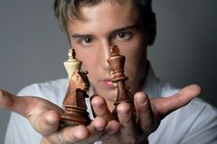 Business is chess. Very handsome young man concentrating on chess figures Royalty Free Stock Photography