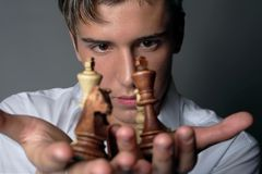 Business is chess. Very handsome young man concentrating on chess figures stock image