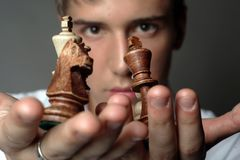 Business is chess. Very handsome young man concentrating on chess figures Royalty Free Stock Photos