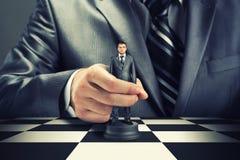 Business chess. Big boss playing chess using businessman stock image