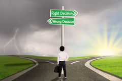 Business child with a sign of right vs wrong decision. Little business child is standing on the road with a sign of right vs wrong decision Stock Images
