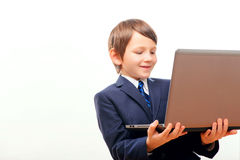 Business child in suit and tie posing with laptop. Small business. Cute little boy in tie and formalwear holding the laptop and smiling while standing against Stock Photo