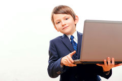 Business child in suit and tie posing with laptop. Small business. Cute little boy in tie and formalwear looking out of the laptop and smiling while standing Royalty Free Stock Photos