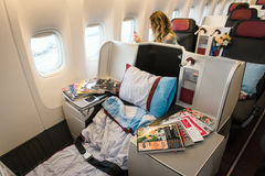 Business class cabin interior of Boeing 777 with woman passenger Stock Photography