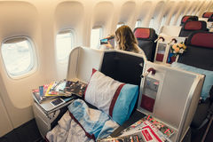 Business class cabin interior of Boeing 777 with woman passenger Stock Images