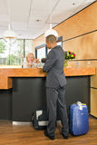 Business class passenger checking in at a hotel reception desk Royalty Free Stock Photos