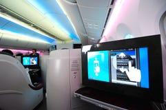 Business-Class-Sitz und während des Betriebsunterhaltungsanlage Bord-Qatar Airways Boeing 787-8 Dreamliner in Singapur Airshow Lizenzfreie Stockfotos