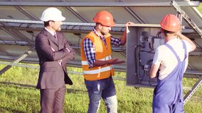Solar panels installation. Business client and two engineers standing at the shield. Working process stock video footage