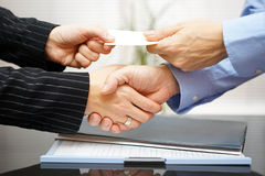 Business clients are exchanging business card  and handshakeing Stock Photography