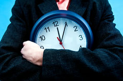 Business clock. Business man with clock in his arms representing time passing by during office hours Royalty Free Stock Image