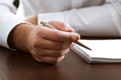 Business closeup. Of businessman with pen and notepad on the table Royalty Free Stock Images