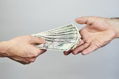 Business closeup of two hands exchanging dollars on grey backgro stock photo