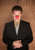 Business Clown. Young businessman with folded clasped hands and clown nose Royalty Free Stock Image