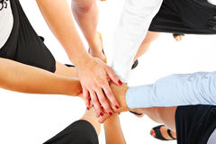 Business co-operation. A picture of five businesswomen having their hands joined in unity over white background Stock Image