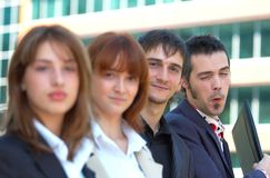 Business Co-Workers 3. Two men and two women in business attire outside an office building.  Focus is on the two men.  The last man has a silly expression and is Royalty Free Stock Image