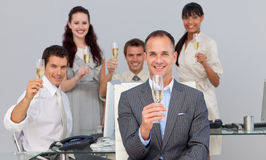 Business co-workers toasting with Champagne. Successful business co-workers toasting with Champagne in the office Royalty Free Stock Image