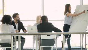 Business coach confident woman giving presentation to multiracial company staff. In modern boardroom gathered different ethnicity and ages workers listens ask stock footage