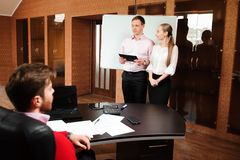 Business coach holding training for staff. Business people in office holding a conference and discussing strategies. Business coach holding training for staff royalty free stock photo