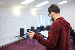 Business coach reading his speech in empty meeting room. Backside. Business coach with beard in brown sweetshirt reading his speech from the clipboard in empty Stock Photos