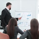 Business coach teaching employees on whiteboard at corporate training.  stock photography