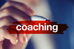 Business coaching concept. Businesswoman highlighting term with red marker pen Stock Images