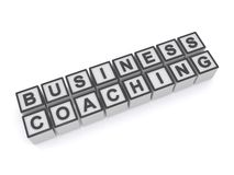 Business coaching. Text 'business coaching' in black uppercase letters on small white cubes side by side, white background stock photos