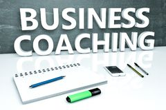 Business Coaching text concept. Business Coaching - text concept with chalkboard, notebook, pens and mobile phone. 3D render illustration Stock Image